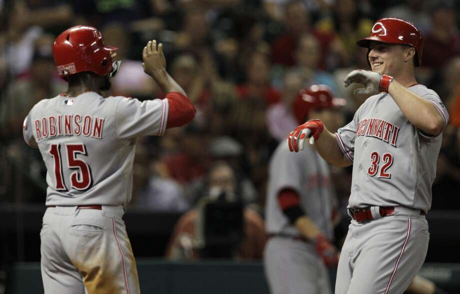 Jay Bruce of the Reds is congratulated by a teammate after hitting a grand slam against the Astros. Photo: Melissa Phillip, Houston Chronicle