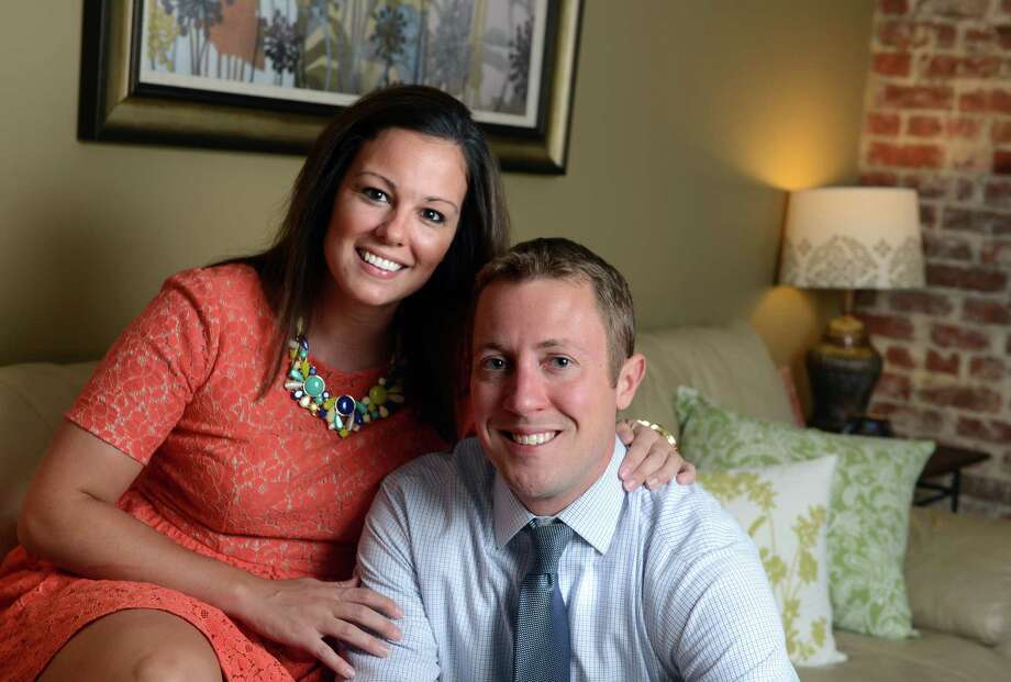 Mikayleigh Ryan and Justin Behn pose for a photo together in their apartment in the Black Rock section of Bridgeport, Conn.  The couple is in the process of moving in together. Photo: Autumn Driscoll / Connecticut Post