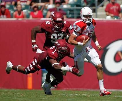 UH freshman quarterback John O'Korn, eluding the rush against Temple, has completed 74 percent of his passes for 340 yards in two games. Photo: Johnny Hanson, Staff / © 2013  Houston Chronicle