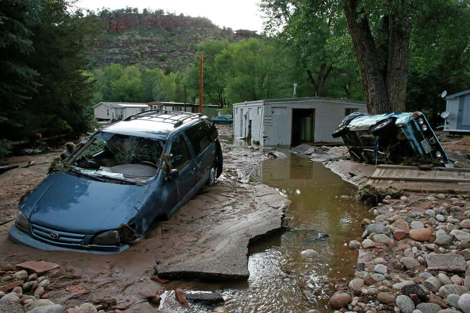 Cars are mired in mud in Lyons, Colo. The flooding hasn't affected the state's skiing industry. Photo: Brennan Linsley, STF / AP