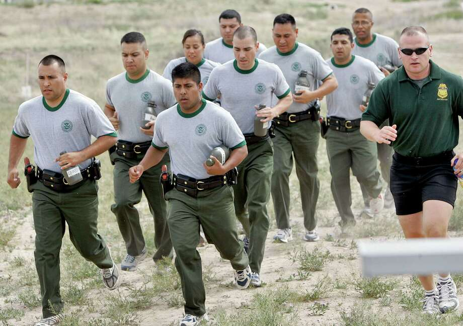 FILE - In this April 5, 2007 file photo, a group of new Border Patrol agents run with their instructor at the Border Patrol Academy in Artesia, N.M. A Sept. 17, 2013 report says a surge in Border Patrol agents hasn't impaired their use-of-force training but that the Department of Homeland Security needs to better track excessive force allegations. (AP Photo/Matt York, File) Photo: Matt York, STF / AP