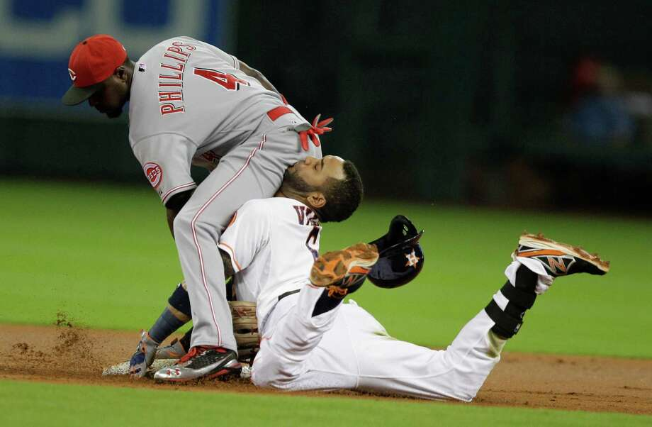 The Astros' Jonathan Villar pays for his decision to try to stretch a single into a double in the first inning as Reds second baseman Brandon Phillips puts an abrupt end to the play. Photo: Melissa Phillip, Staff / © 2013  Houston Chronicle