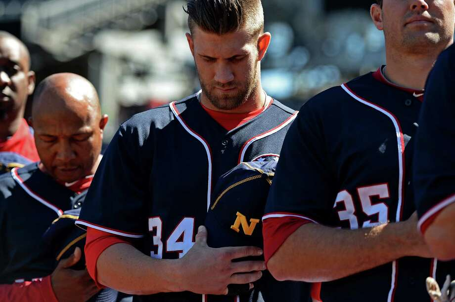 Bryce Harper holds a Navy hat while the Nationals observe a moment of silence for the victims of the Navy Yard shooting before starting a doubleheader sweep. Photo: Patrick Smith, Stringer / 2013 Getty Images