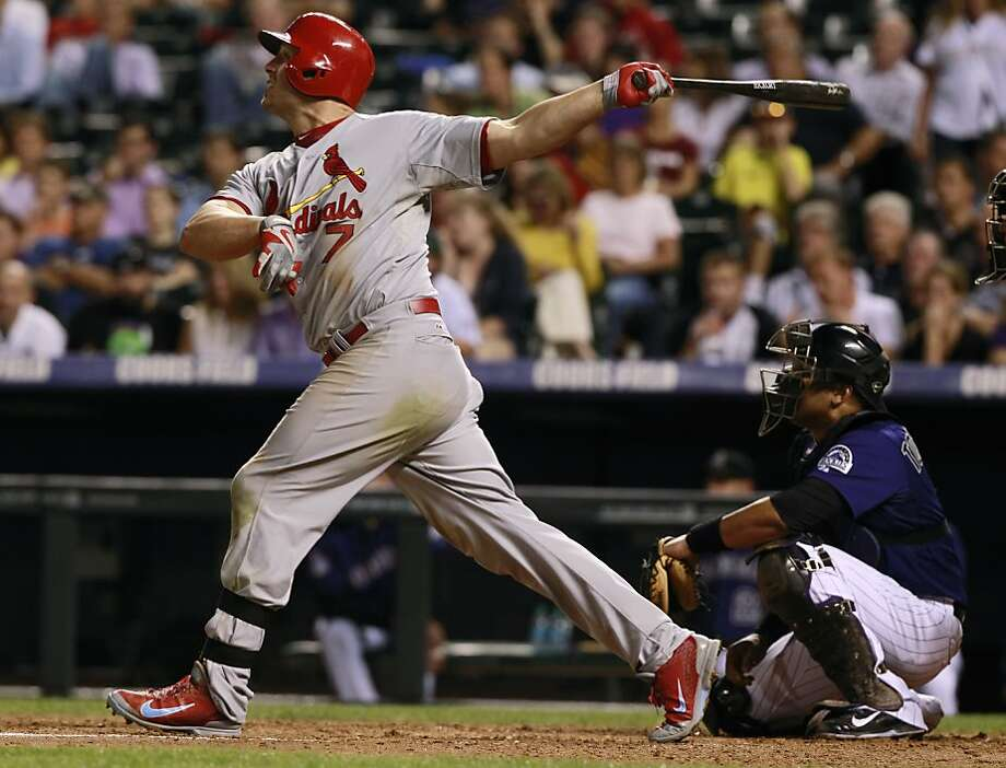 Matt Holliday, right, had four hits, including a two-run homer, to help the Cardinals take  sole possession of first place in the NL Central with an 11-4 victory at Colorado on Tuesday night. Photo: David Zalubowski, Associated Press