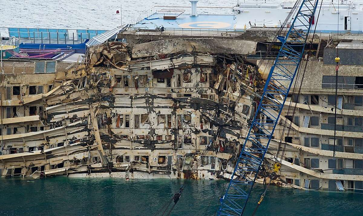 ISOLA DEL GIGLIO, ITALY - SEPTEMBER 17: The severely damaged side of the stricken Costa Concordia is visible after the parbuckling operation succesfully uprighted the ship around 4 am on September 17, 2013 in Isola del Giglio, Italy. Work began yesterday to right the stricken Costa Concordia vessel, which sank on January 12, 2012. If the operation is successful, it will then be towed away and scrapped. The procedure, known as parbuckling, has never been carried out on a vessel as large as Costa Concordia before. (Photo by Marco Secchi/Getty Images) *** BESTPIX ***