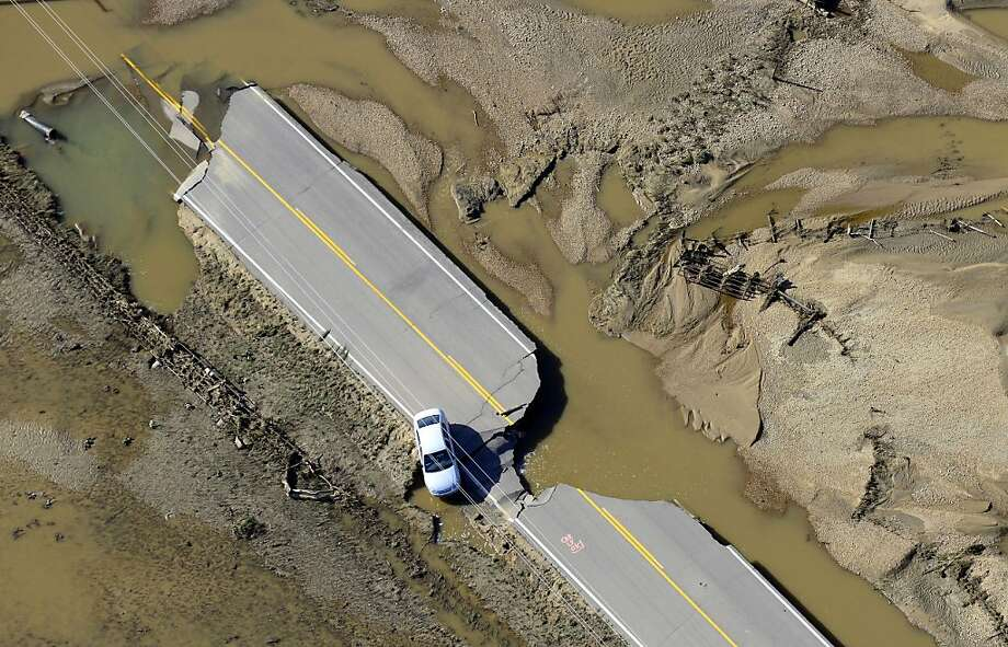 An abandoned car lies off a road devastated by flood waters along the South Platte River east of Greeley, Colo, Tuesday, Sept. 17, 2013.  Northern Colorado's broad agricultural expanses are especially affected, with more than 400 lane-miles of state highway and more than 30 bridges destroyed or impassable. (AP Photo/John Wark) Photo: John Wark, Associated Press