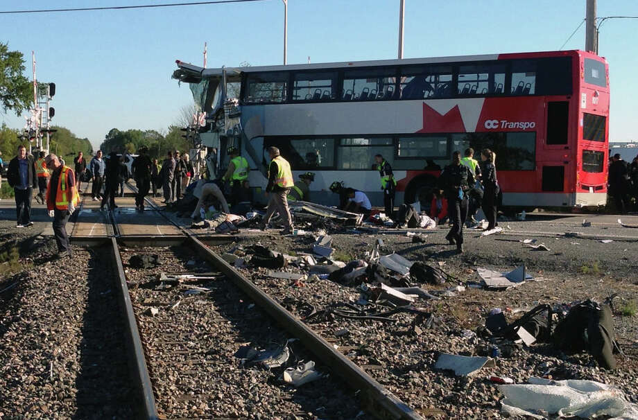 "Officials respond to the scene where a city bus collided with a Via Rail passenger train at a crossing in Ottawa, Ontario, Wednesday, Sept. 18, 2013. An Ottawa Fire spokesman told CP24 television there are ""multiple fatalities"" and a number are injured from the bus but no injuries on the train. Photo: The Canadian Press, Terry Pedwell"
