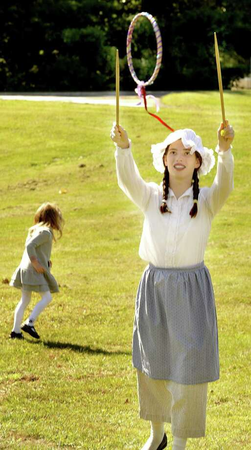 """Maren Brady, 13, plays a game called """"Graces,"""" in costume, during Children's Day at the Little Red Schoolhouse in Newtown Sunday, Sept. 18, 2011. This year's Children's Day event will be Sunday, Oct. 6. Photo: Michael Duffy"""