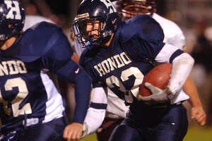 Hondo running back Gabe Hackebeil moves around his left end to score a touchdown in the first half against Devine Friday in Hondo. HONDO DEVINE HIGH SCHOOL FOOTBALL TOM REEL/STAFF NOVEMBER 7, 2003.