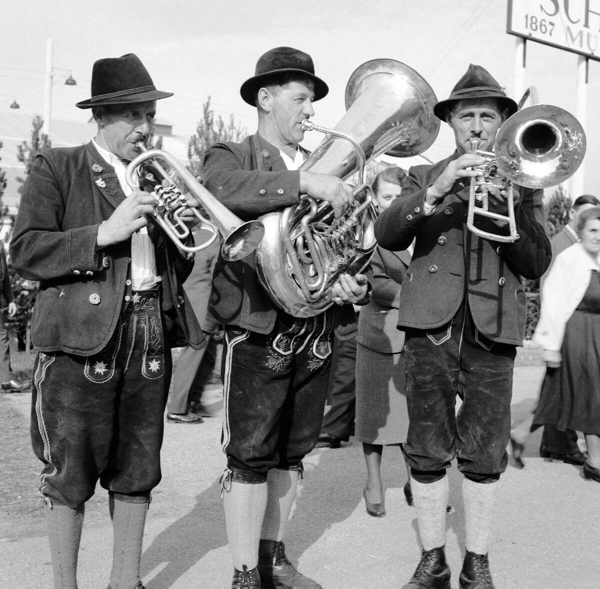 A brass trio in traditional Bavarian dress playing for beer drinkers at the Oktoberfest, Munich.
