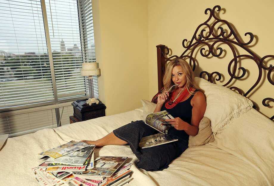 Shelbi Jary relaxes with magazines in her downtown home. Photo: Edward A. Ornelas / San Antonio Express-News
