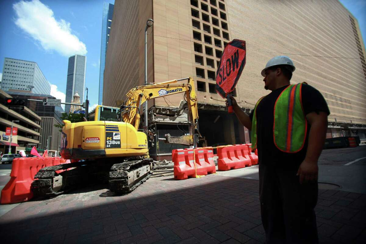 Mauro Valdez directs street traffic as heavy machinery is shuffled around the downtown Macy's in preparation for the implosion next week on Thursday, Sept. 12, 2013, in Houston. ( Mayra Beltran / Houston Chronicle )