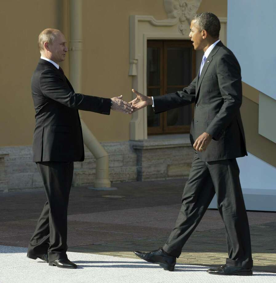 "FILE - In this Sept. 5, 2013, President Barack Obama reaches to shakes hands with Russia's President Vladimir Putin during arrivals for the G-20 summit in St. Petersburg, Russia. Obama welcomed an agreement reached with Russia Saturday, Sept. 14, 2013, to secure and destroy Syria's chemical weapons stockpile, but warned that the U.S. remains prepared to act if the attempt at a diplomatic solution fails. ""I welcome the progress made between the United States and Russia through our talks in Geneva, which represents an important, concrete step toward the goal of moving Syria's chemical weapons under international control so that they may ultimately be destroyed,"" Obama said Saturday. (AP Photo/Pablo Martinez Monsivais, Pool File) Photo: Pablo Martinez Monsivais, Associated Press / AP Pool"