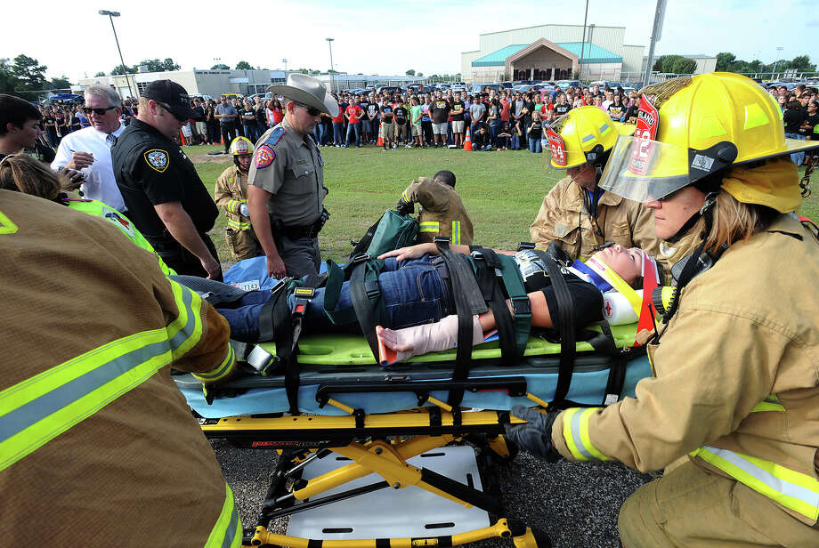 In a dramatic interpretation of a alcohol fueled car accident, Brandon Dial is carried by stretcher to an awaiting helicopter at Nederland High School on Wednesday. The staged event is designed to show students the impact of drinking and driving.  Several students, fire and police officials acted out the sobering scenario that included one mock fatality, several injuries and an arrest.  Photo taken Wednesday, September 18, 2013 Guiseppe Barranco/The Enterprise Photo: Guiseppe Barranco, STAFF PHOTOGRAPHER / The Beaumont Enterprise