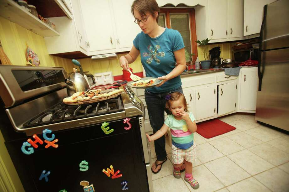 Jo Ehlers hands around the kitchen as her mom, Andrea Weigle, serves pizza she made for her family in Raleigh, North Carolina, on August 14, 2013. (Juli Leonard/Raleigh News & Observer/MCT) ORG XMIT: 1143159 Photo: Juli Leonard / Raleigh News & Observer