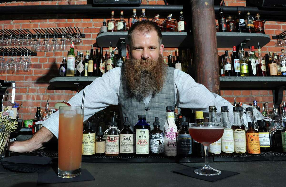 The Speakeasy . Basement of City Beer Hall on corner Howard and Lodge Streets, Albany. Bartender Robert Mack poses aftermaking a simplified home version of the Jack Rose cocktail, on left, and the original version he makes at The Speakeasy Thursday, Sept. 12, 2013 in Albany, N.Y. The Speakeasy is in basement of City Beer Hall on Howard and Lodge Streets. (Lori Van Buren / Times Union)