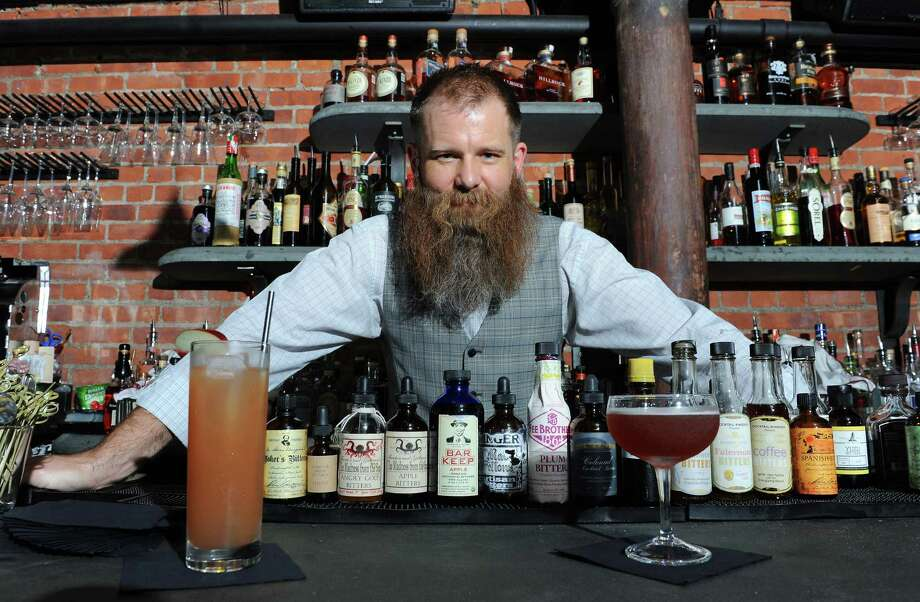 The Speakeasy. Basement of City Beer Hall on corner Howard and Lodge Streets, Albany.Bartender Robert Mack poses aftermaking a  simplified home version of the Jack Rose cocktail, on left, and the original version he makes at The Speakeasy Thursday, Sept. 12, 2013 in Albany, N.Y. The Speakeasy is in basement of City Beer Hall on Howard and Lodge Streets.  (Lori Van Buren / Times Union) Photo: Lori Van Buren / 00023831A