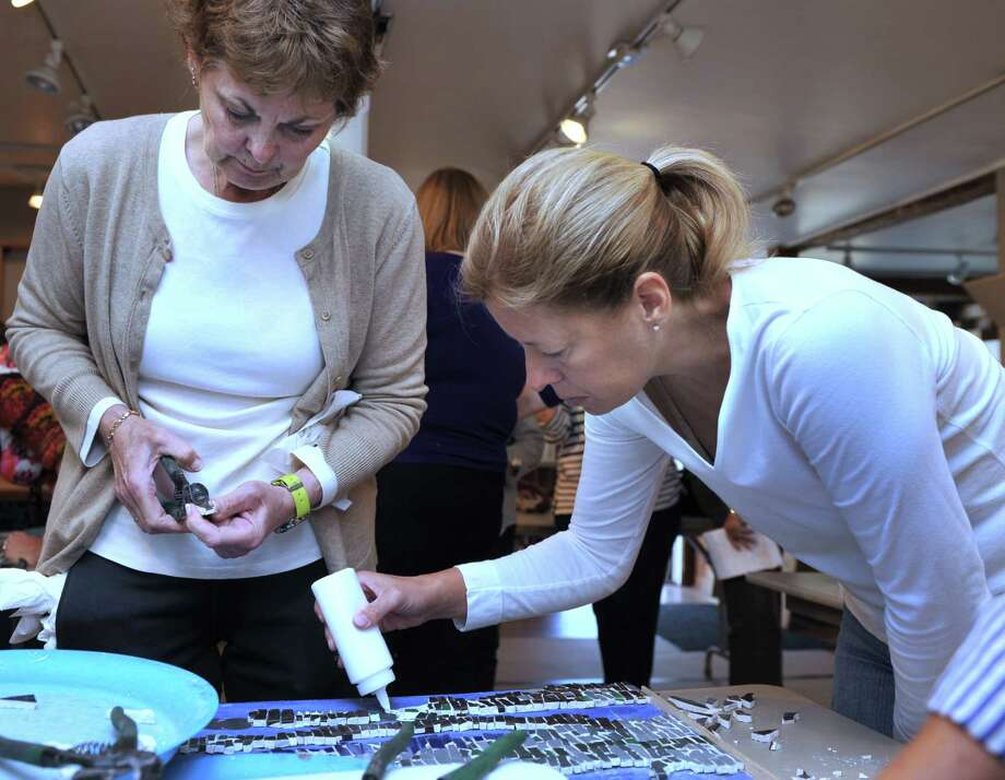 "Pam Willmer, of New Milford, left, and Marie Bray, of Brookfield, work on a mosaic Wednesday. The Brookfield Commission on the Arts in Brookfield, Conn., is doing a mosaic project for Town Hall. Volunteer artists are working on a project titled, ""Reflections in Mosaic.""  It's being created at the Brookfield Craft Center, Wed. Sept. 18, 2013. Photo: Carol Kaliff / The News-Times"