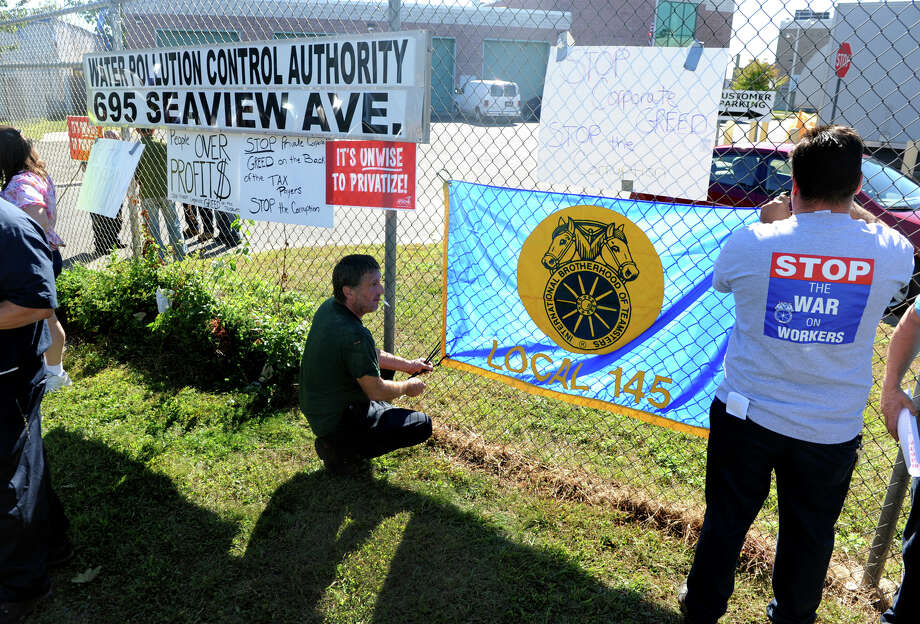Union members hang a flag for Local 145 before the start of a rally and press conference to make known their concerns with a change in management at the Water pollution Control Authority on Seaview Avenue in Bridgeport, Conn. on Wednesday September 18, 2013. Hanging the flag is Ljubo Hribar and Mark Pagnozzi, at right. Photo: Christian Abraham / Connecticut Post