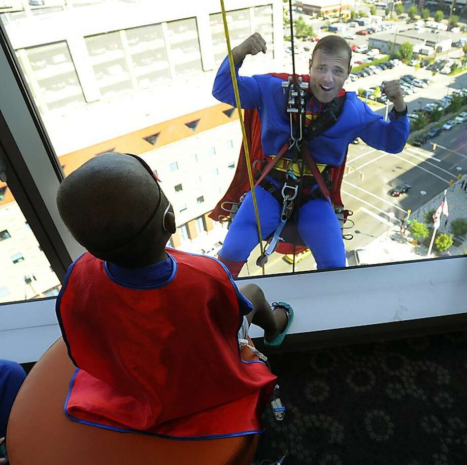 But why do you need the rope, Superman? Five-year-old Reginae Bush watches the Man of Steel flex as he rappels 