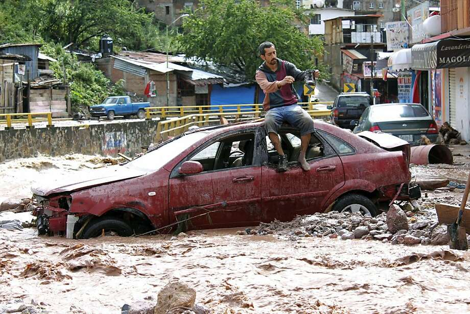 Resort cut off: A man sits rests atop a car while trying to cross a flooded street in Chilpancingo, Mexico's Guerrero state. 