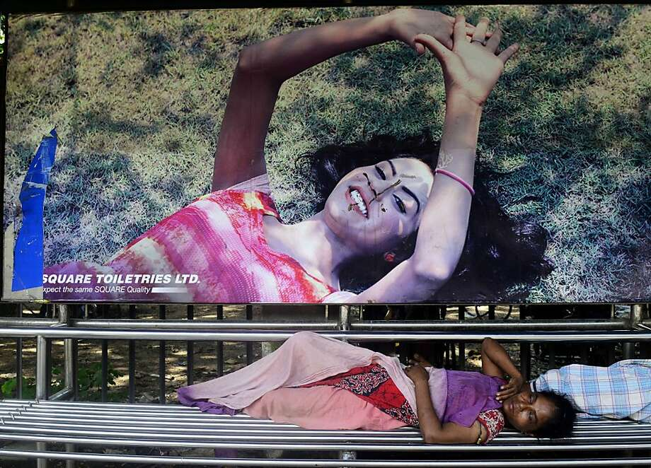 Reclining women:A Bangladeshi street person sleeps at a bus stop in Dhaka. Photo: Munir Uz Zaman, AFP/Getty Images