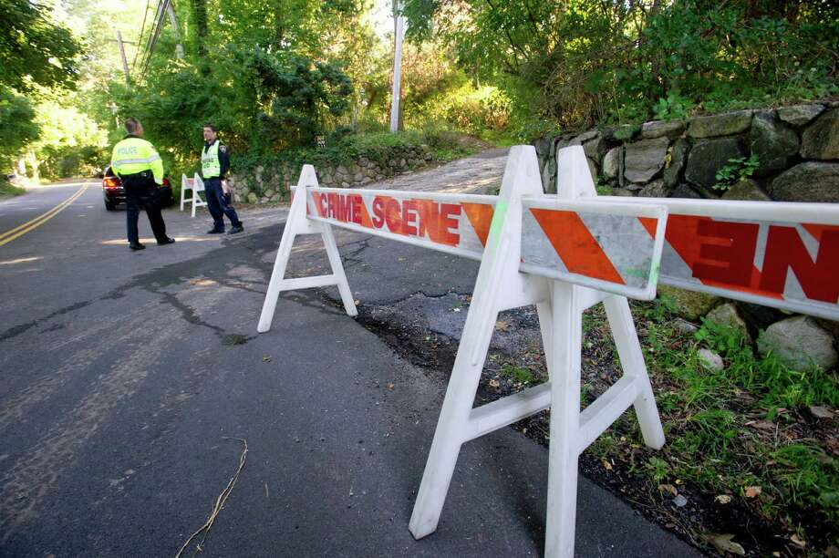 Police officers stand at the bottom of the driveway at 305 Webbs Hill Road in Stamford, Conn., on Wednesday, Sept. 18, 2013, the day after the home exploded. The blast is believed to have been caused by a propane leak in the home. Photo: Lindsay Perry / Stamford Advocate