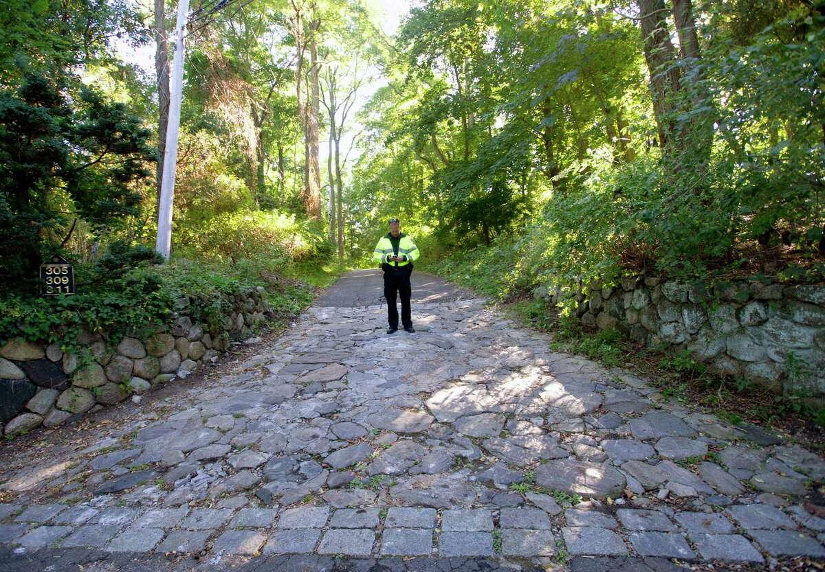 Police officers stand at the bottom of the driveway at 305 Webbs Hill Road in Stamford, Conn., on Wednesday, Sept. 18, 2013, the day after the home exploded. The blast is believed to have been caused by a propane leak in the home.