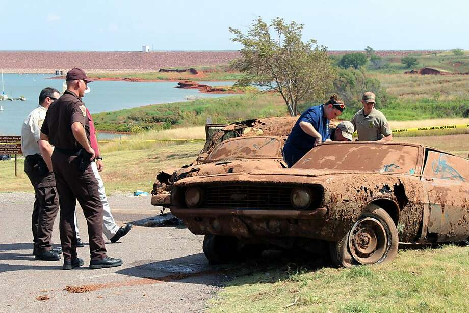 From lake's depths, a mystery emerges:Investigators examine two decades-old cars pulled from Foss Lake, Okla., by a dive team. The Oklahoma State Medical Examiner's Office said skeletal remains of six bodies were recovered from the cars. Photo: Larissa Graham, Associated Press