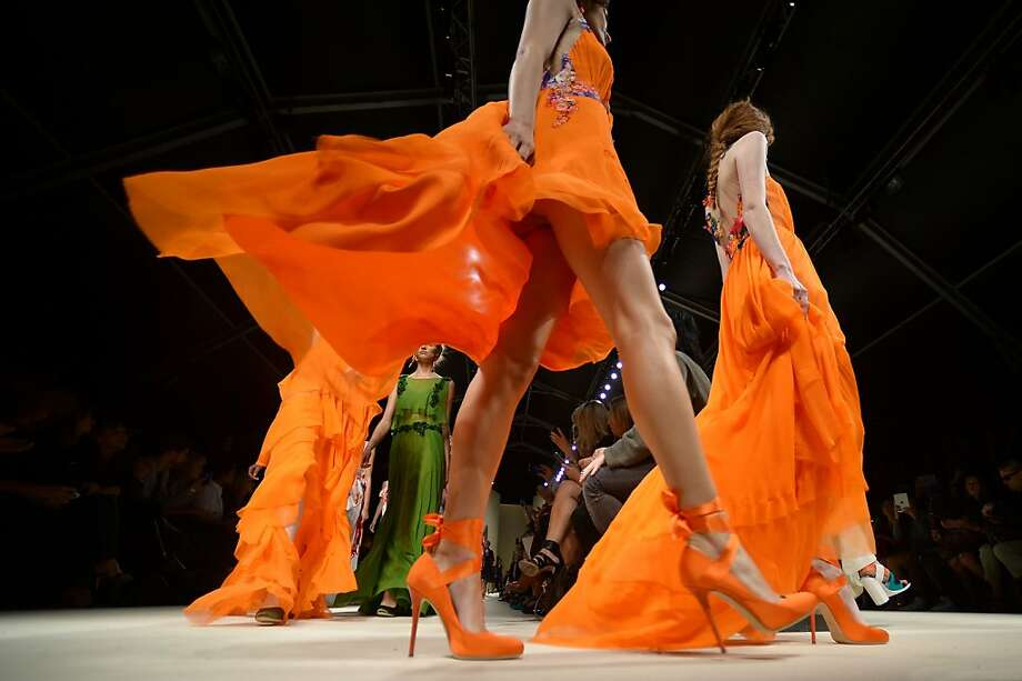 Orange appeal:Models show wispy designs from Alberta Ferretti as part of the Spring/Summer 2014 ready-to-wear collections during Milan Fashion Week. Photo: Filippo Monteforte, AFP/Getty Images