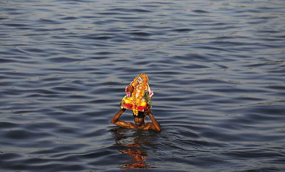 Dunkin' devotee:A Hindu worshipper carries an idol of the elephant-headed god Ganesha before immersing it in the River 