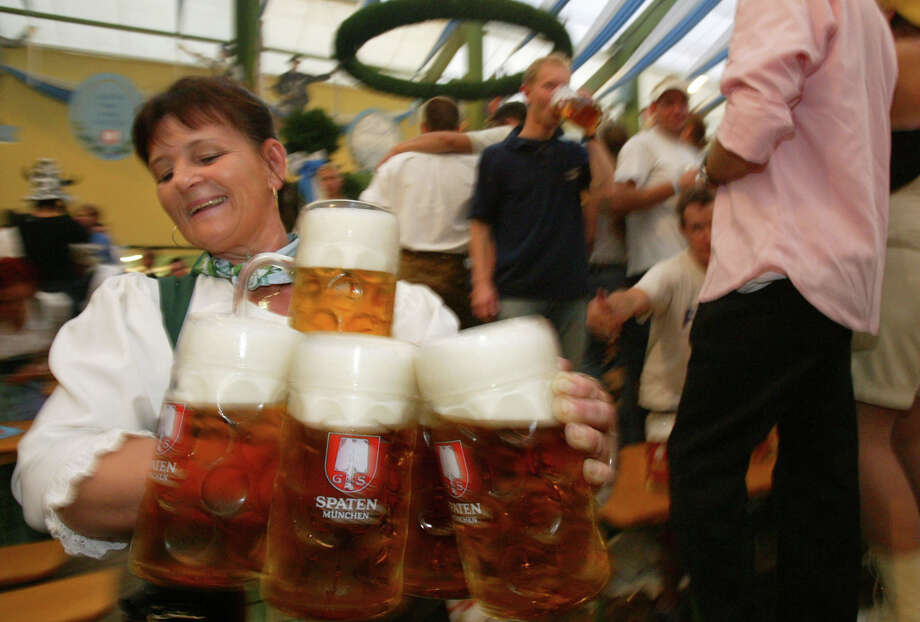 A waitress carries liter full mugs of beer to revelers at the annual Oktoberfest celebration Sept. 21, 2003 in Munich, Germany. Photo: Sean Gallup, Getty Images / 2003 Getty Images