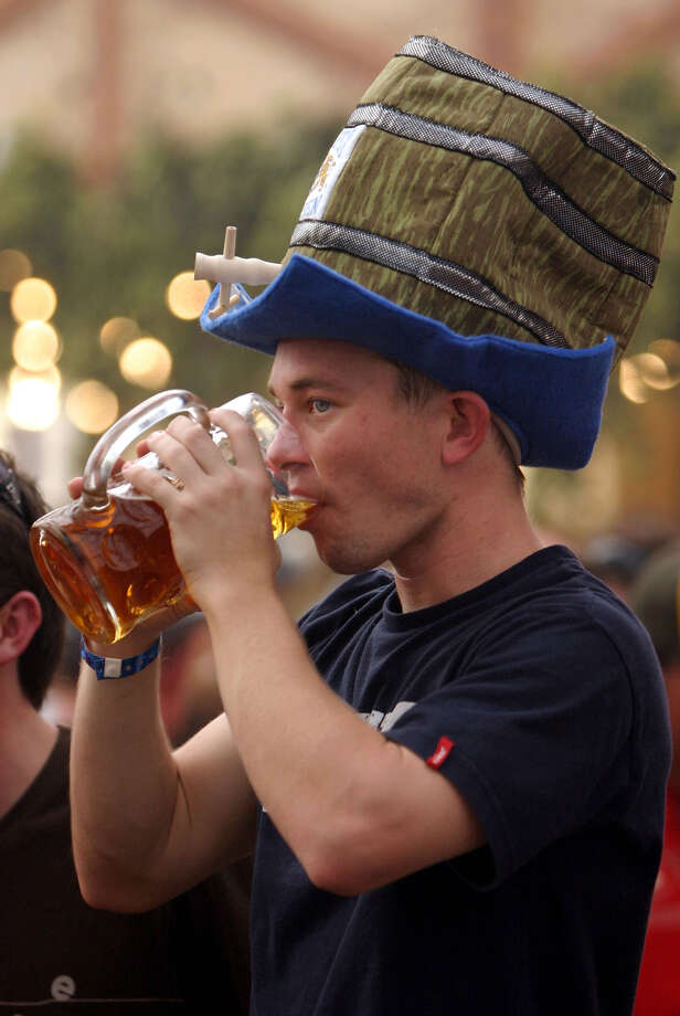 A young reveler wearing a hat in the shape of a beer keg drinks beer from a one liter mug Sept. 18, 2004 at the Hofbraeuhaus tent on the opening day of the 2004 Oktoberfest in Munich, Germany. Photo: Sean Gallup, Getty Images / 2004 Getty Images