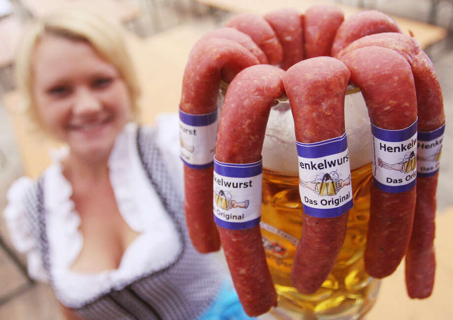 A waitress presents a beer mug with sausages hanging on it during preparations of the Oktoberfest. Photo: OLIVER LANG, Getty Images / 2007 AFP