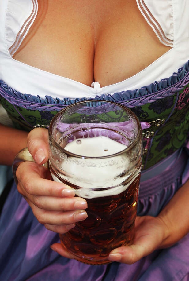A woman wearing a traditional Bavarian Dirndl dress holds a beer mug during the opening day of the Oktoberfest 2011 beer festival. Photo: Alexandra Beier, Getty Images / 2011 Getty Images
