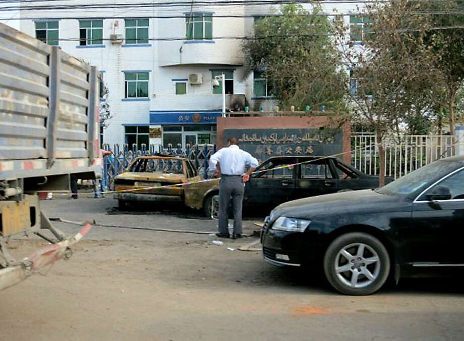 FILE - This June 27, 2013 file photo shows destroyed vehicles in front of a police station in Lukqun township, Xinjiang, China, a day after a violent rampage occurred. China has sentenced three men to death over a June attack in the restive northwestern region of Xinjiang blamed on Islamic extremists in which 24 police and civilians and 13 militants were killed. The official Xinhua News Agency said Friday, Sept. 13, 2013 another man was sentenced to 25 years in prison for his role in the June 26 violence. All four were found guilty of murder and being members of a terrorist organization and sentenced Thursday by a court in the city of Turfan at the end of a one-day trial. (AP Photo/Kyodo News, File) JAPAN OUT, MANDATORY CREDIT Photo: Associated Press