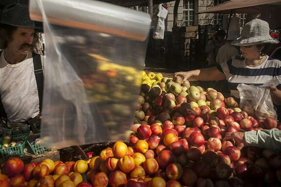Produce shoppers pick out apples at the Heart of the City Farmers' Market at UN Plaza in San Francisco on September 18th 2013.