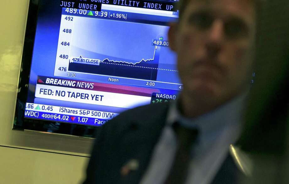 A television monitor on the floor of the New York Stock Exchange shows the decision of the Federal Reserve, Wednesday, Sept. 18, 2013.  The Federal Reserve has decided against reducing its stimulus for the U.S. economy, saying it will continue to buy $85 billion a month in bonds because it thinks the economy still needs the support. (AP Photo/Richard Drew) ORG XMIT: NYRD114 Photo: Richard Drew / AP