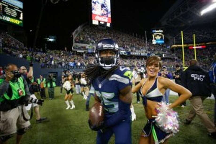 Seattle Seahawks Sea Gal cheerleader Jessica dances with Richard Sherman. (Otto Greule Jr/Getty Images)