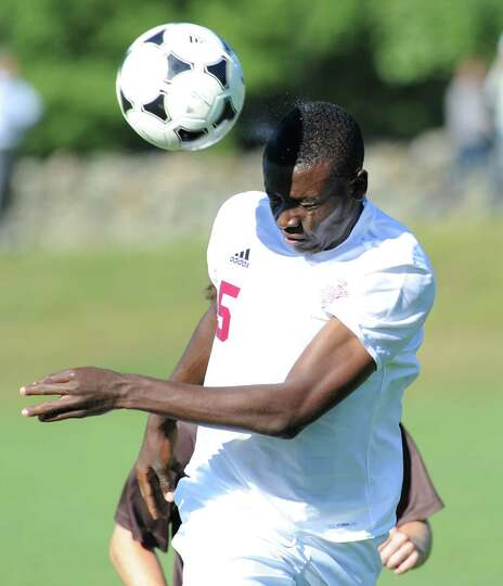Prosper Figbe (# 5) of Loomis Chaffee heads the ball during the soccer match between Brunswick Schoo