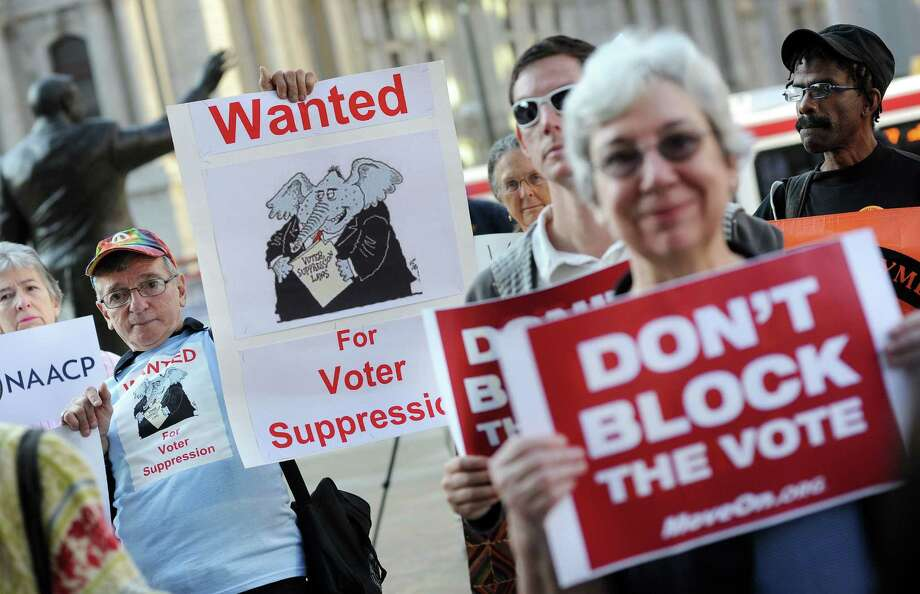 Demonstrators hold signs during an anti-voter ID rally in Philadelphia. Express-News readers share their concerns about voter ID laws. Photo: File Photo, McClatchy-Tribune