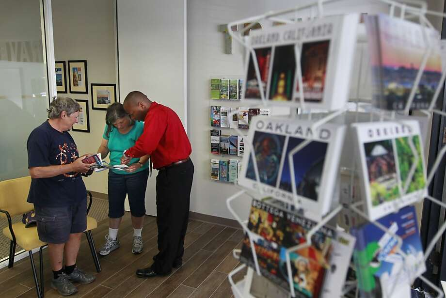 Coordinator Bostyon Johnson (right) shares information with Oakland residents Gilles and Martha Bureau at the Visit Oakland Center at Jack London Square as the polishing of Oakland's image goes into full swing. Photo: Michael Macor, The Chronicle