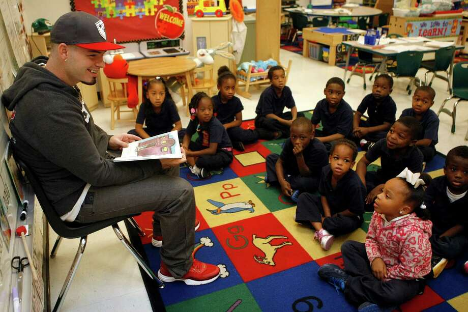 "Houston area rapper Paul Wall smiles as a student tells him that her ""uncle is a rapper too,"" as Wall read to a group of kindergarten students at Bastian Elementary School as part of the Wade Smith Foundation's Reading With the Pros Program Tuesday, Oct. 30, 2012, in Houston. Wall joined the Houston Texans' guard Wade Smith, Owen Daniels, Antonio Smith, Ryan Harris, Shaun Cody, Andrew Gardner and Tackle Derek Newton, as well as almost a dozen University of Houston students at both Alcott and Bastian Elementary Schools for a morning of reading with students, in an effort to promote literacy and education. Staff from nearby Johnson Public Library was also on hand again to complete library card registrations on-site. For more information visit: www.wadesmithfoundation.org ( Johnny Hanson / Houston Chronicle ) Photo: Johnny Hanson, Staff / © 2012  Houston Chronicle"