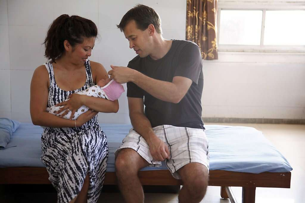 Jennifer Benito-Kowalski and Steve Kowalski bond with their baby Kyle Benito Kowalski while waiting for a hotel car after Kyle was released from the Apara Nursing Home in Anand, India, Friday, May 24, 2013. The car never arrived, so, the Kowalskis gave up and walked to the Akanksha Infertility Clinic to phone the hotel again. Photo: Nicole Fruge, The Chronicle