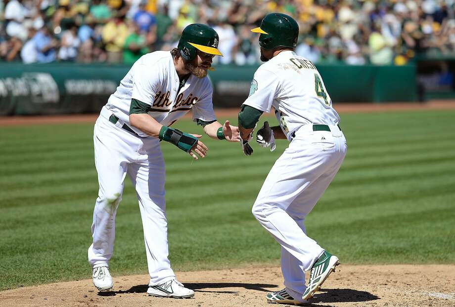 OAKLAND, CA - SEPTEMBER 18:  Coco Crisp #4 and Josh Reddick #16 of the Oakland Athletics celebrate after Crisp hit a two-run homer during the third inning against the Los Angeles Angels of Anaheim at O.co Coliseum on September 18, 2013 in Oakland, California.  (Photo by Thearon W. Henderson/Getty Images) Photo: Thearon W. Henderson, Getty Images