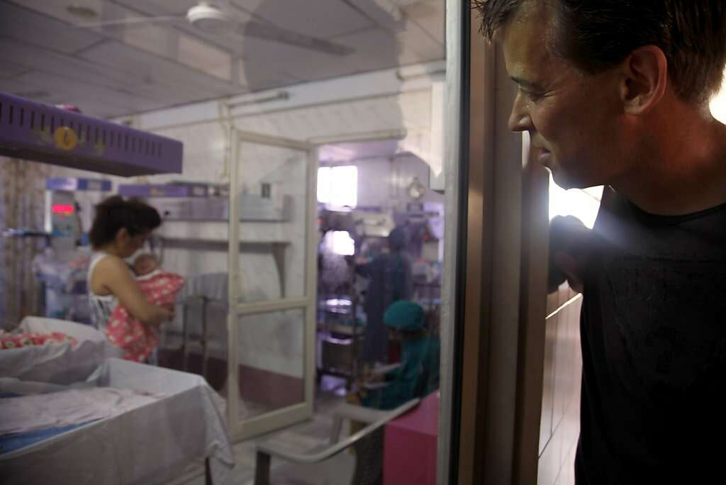 Steve Kowalski watches his with Jennifer Benito-Kowalski holds their son Kyle Benito Kowalski in the nursery at the Apara Nursing Home in Anand, India, Friday, May 24, 2013. Photo: Nicole Fruge, The Chronicle