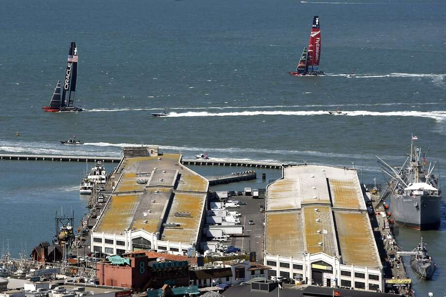 Emirates Team New Zealand and Oracle Team USA pass in front of Fisherman's Wharf as they tack upwind during race number eleven of the America's Cup Finals in San Francisco, California Wednesday, September 18, 2013. Photo: Michael Short, The Chronicle