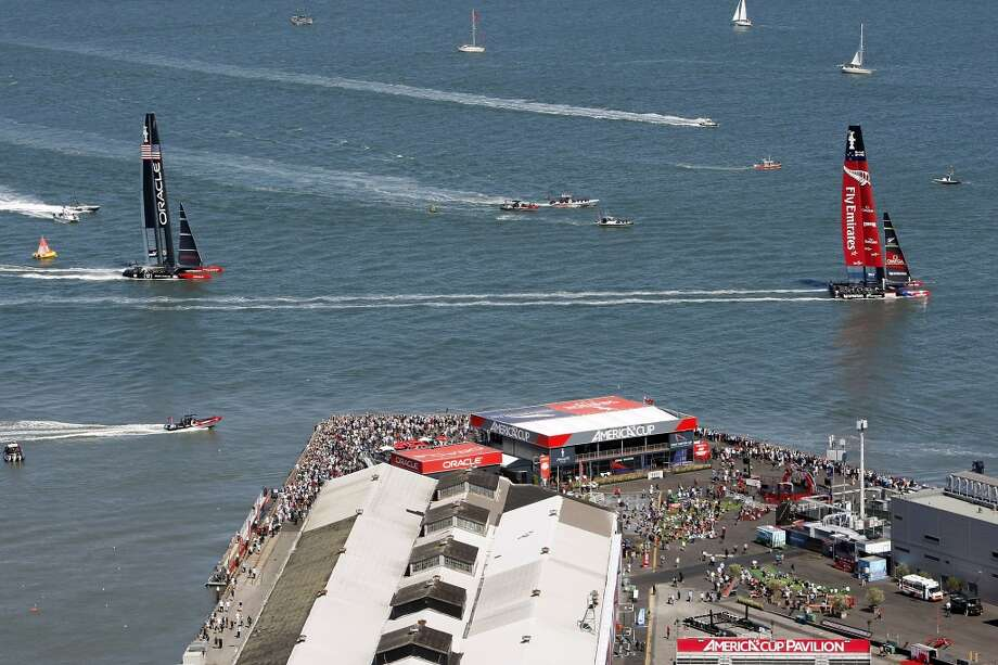 Emirates Team New Zealand, right, passes the America's Cup Pavilion after crossing the finish line ahead of Oracle Team USA to win race number eleven of the America's Cup Finals in San Francisco, California Wednesday, September 18, 2013. Photo: Michael Short, The Chronicle