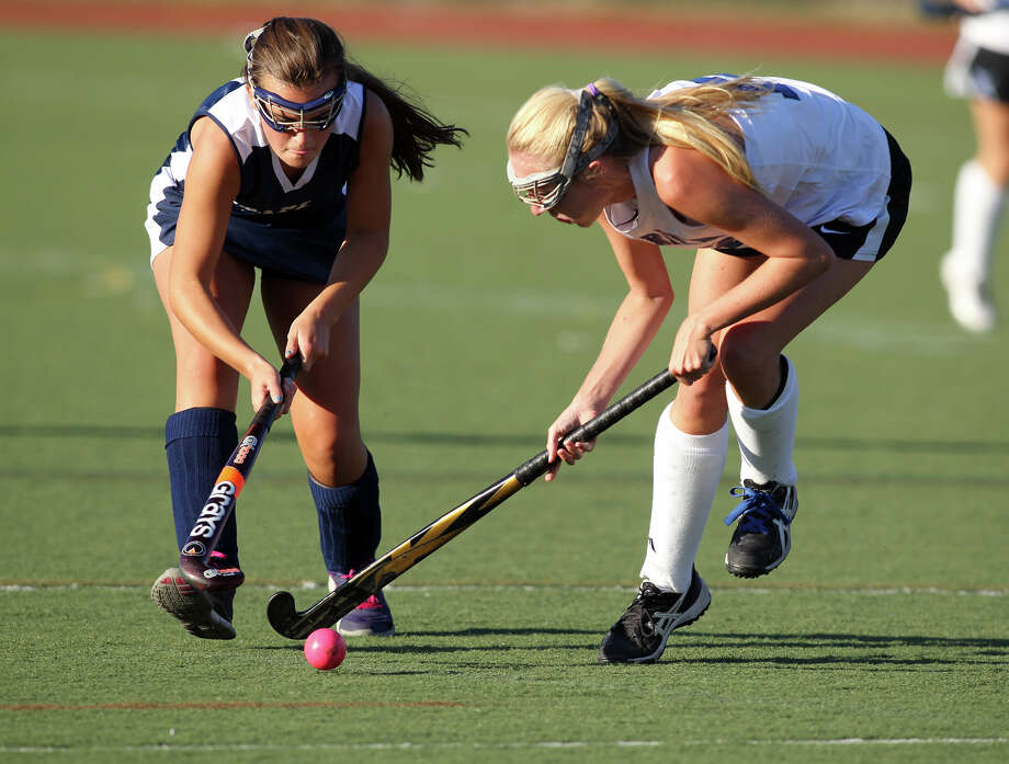 Staples player Meg Fay and Darien counterpart Claire Culliton battle for possession of the ball during a field hockey match at Darien High School on Wednesday afternoon, Sept. 18, 2013. Darien won the game, 3-0. Photo: J. Gregory Raymond / Stamford Advocate Freelance;  © J. Gregory Raymond