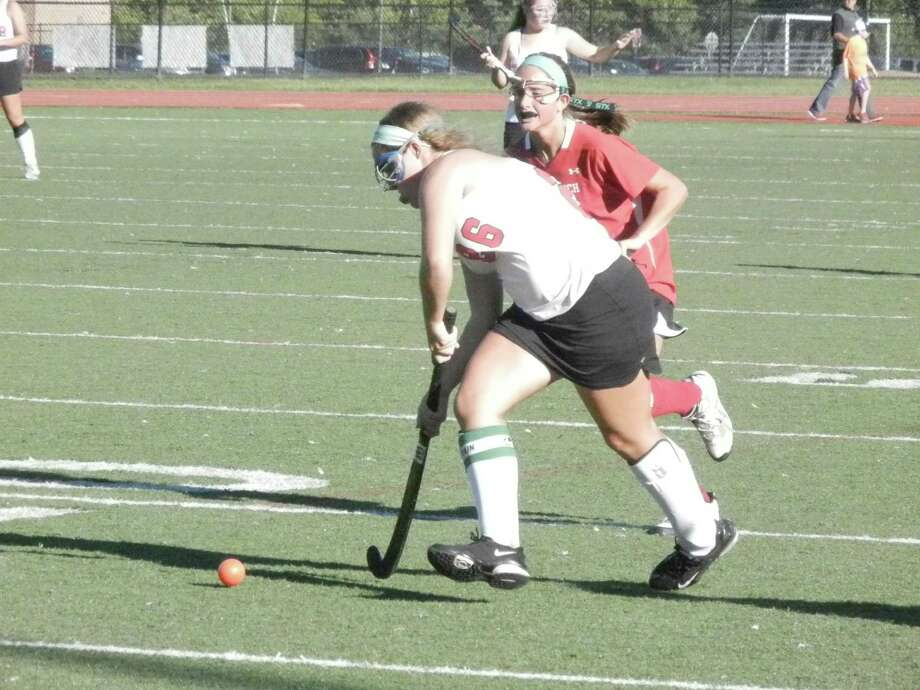 Fairfield Warde field hockey player Erin Hines (26) is challenged by Greenwich's Mehan Collins duirng Greenwich's 3-1 victory over the Mustangs at Tetreau/Davis Field in Fairfield on Wednesday, Sept. 18. Photo: Reid L. Walmark / Fairfield Citizen